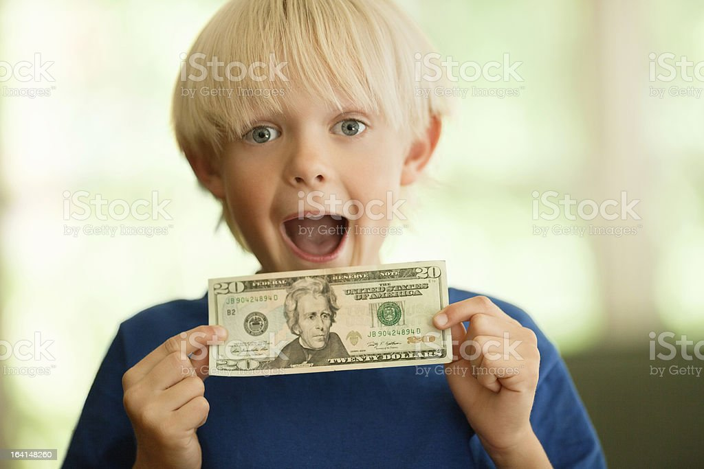 Shocked Little Boy With A Twenty Dollar Bill stock photo