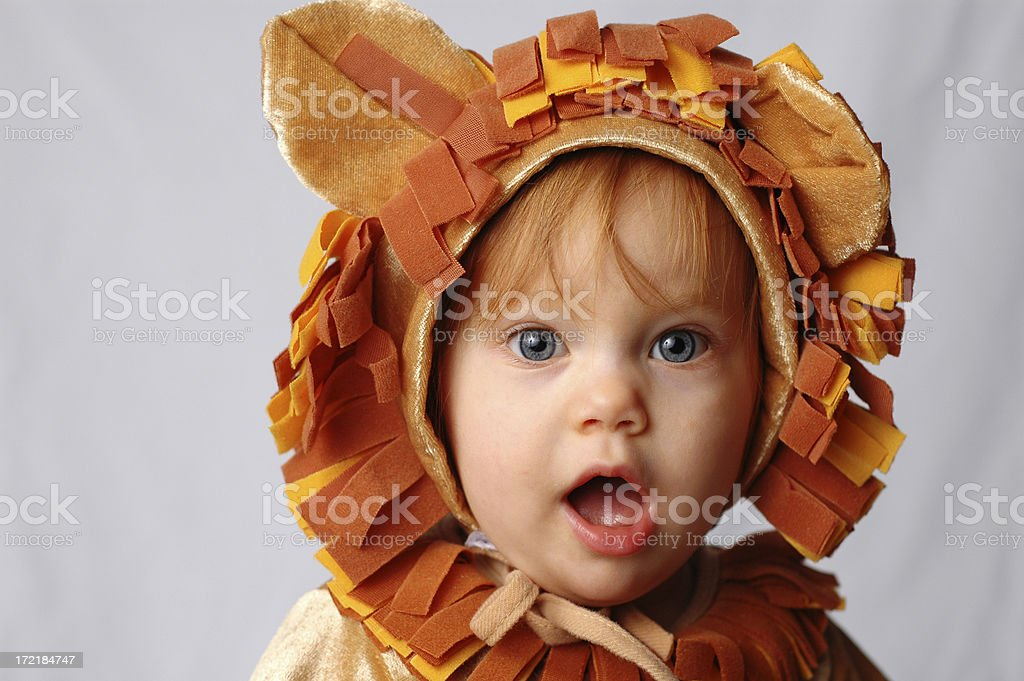 """Shocked Little Lion """"Cute, little baby with red hair and blue eyes dressed in a lion costume and looking shocked!Sales pitch: Shocking deals...and we're not lion!"""" 12-17 Months Stock Photo"""