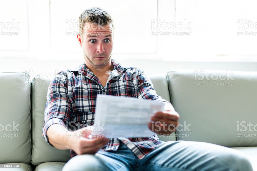 Shocked man holding some documents on sofa livingroom stock photo