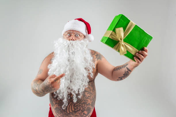 shocked man in christmas hat showing gift - naked santa claus stock pictures, royalty-free photos & images