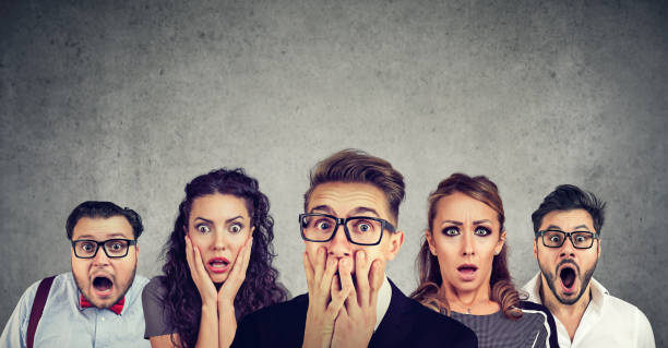 Shocked man in glasses and his scared friends stock photo