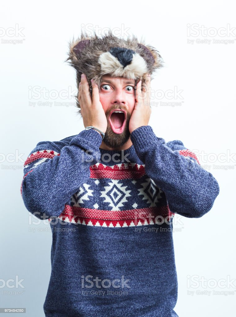 Shocked man in warm clothing Portrait of man in winter outfit looking shocked on white background. Hands on face with mouth open. Adult Stock Photo