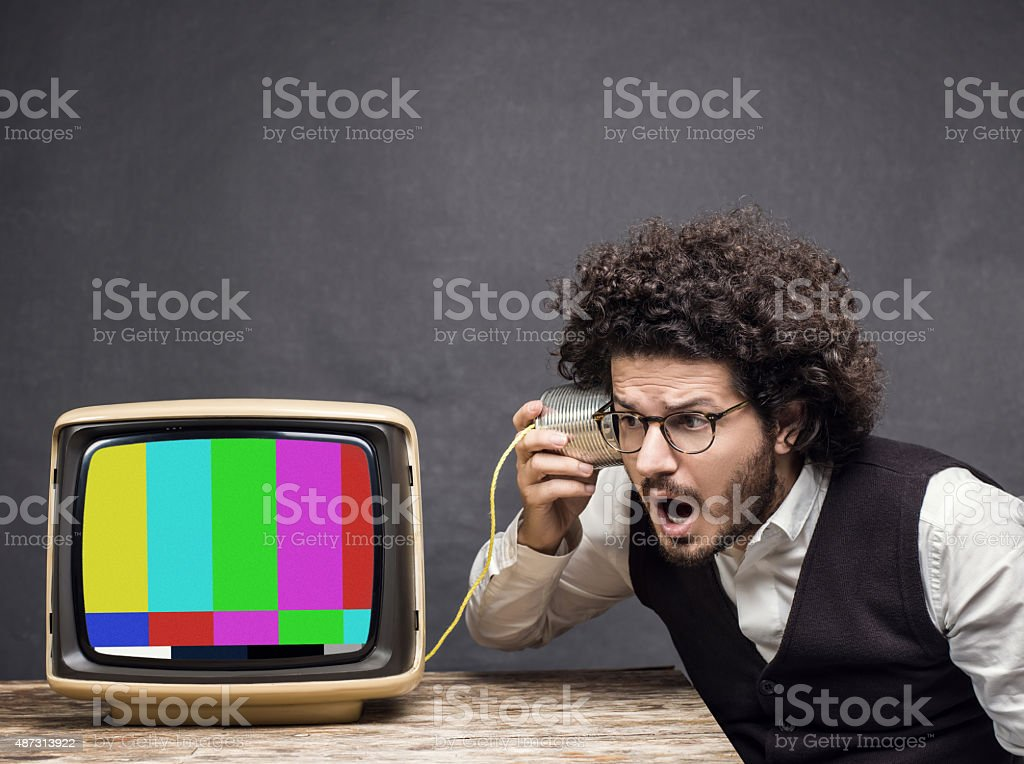 Shocked man listening censored news from vintage television stock photo