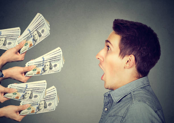 Shocked man looking at hands offering money Shocked man looking at many hands offering money dollar bills borrowing stock pictures, royalty-free photos & images