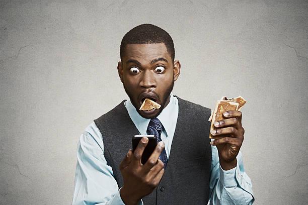 schockiert mann lesen nachrichten am telefon beim essen - kündigung arbeitsvertrag stock-fotos und bilder