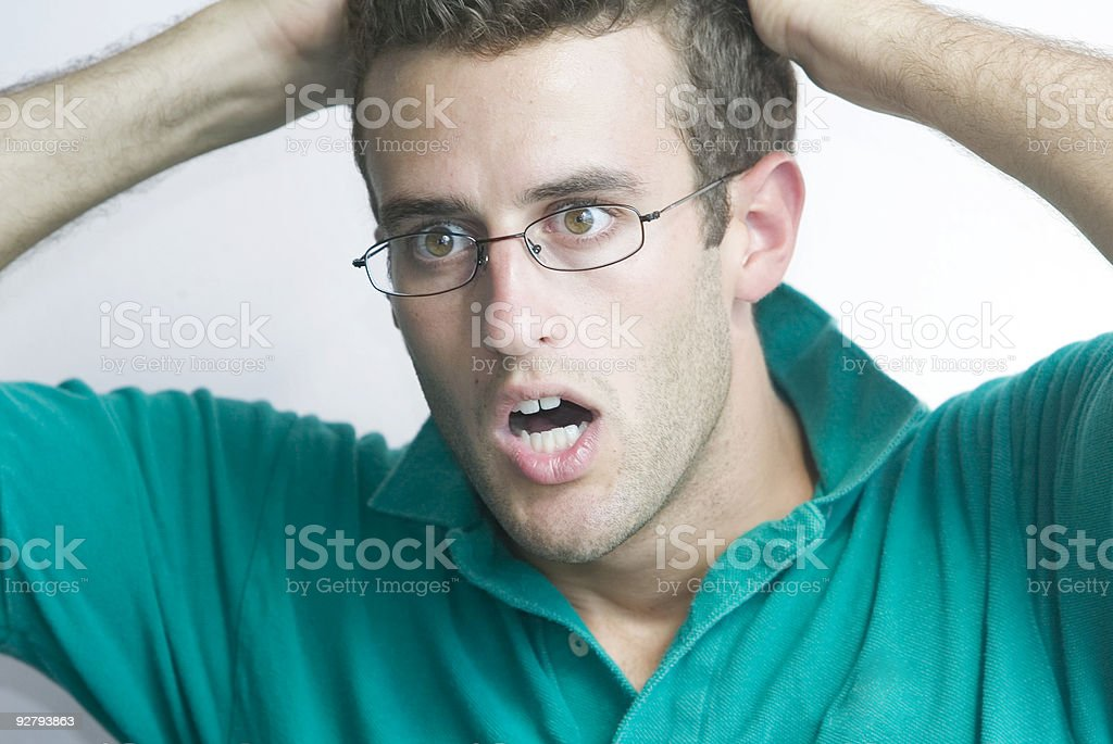 Shocked man wearing glasses with his hands on his head royalty-free stock photo