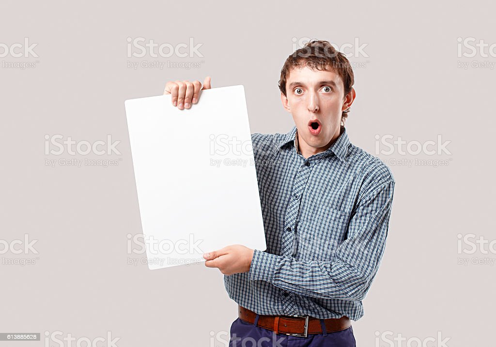 shocked man with a sheet of white paper in hands stock photo