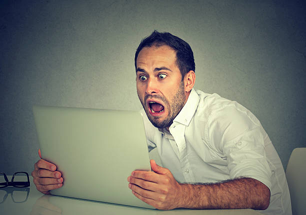 shocked man with laptop computer sitting at table stock photo