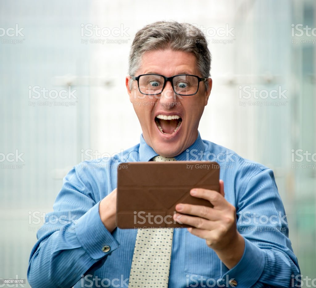 Shocked Middle-aged Business Man Using Touchpad stock photo