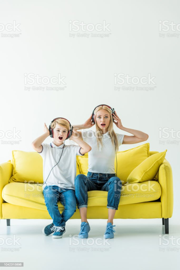 shocked mother and son listening music with headphones and touching heads on yellow sofa on white stock photo