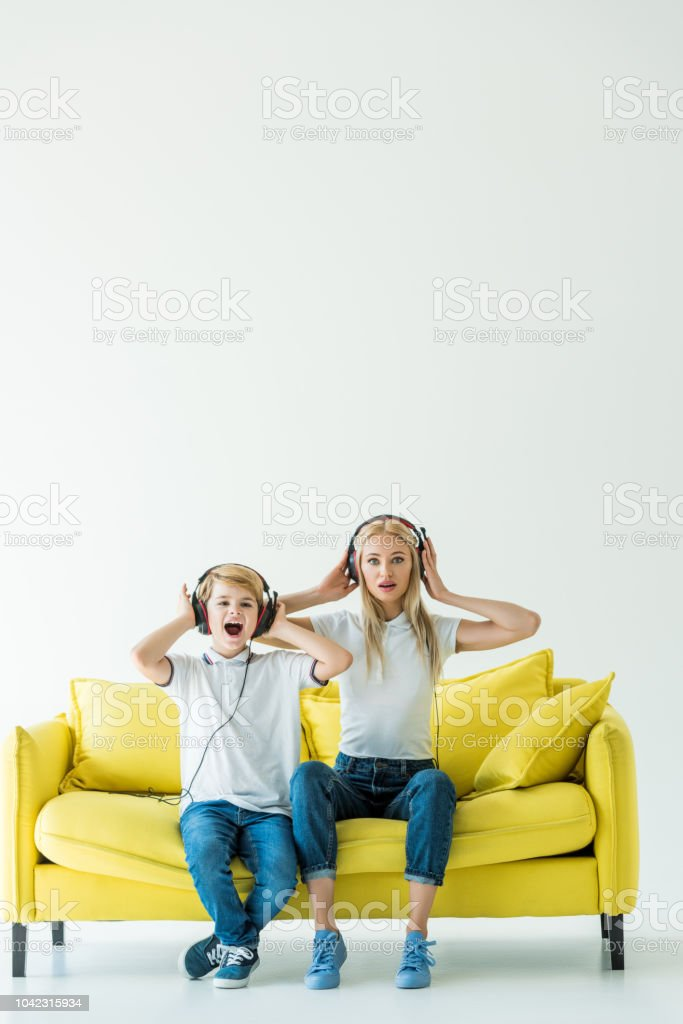 shocked mother and son listening music with headphones on yellow sofa on white stock photo