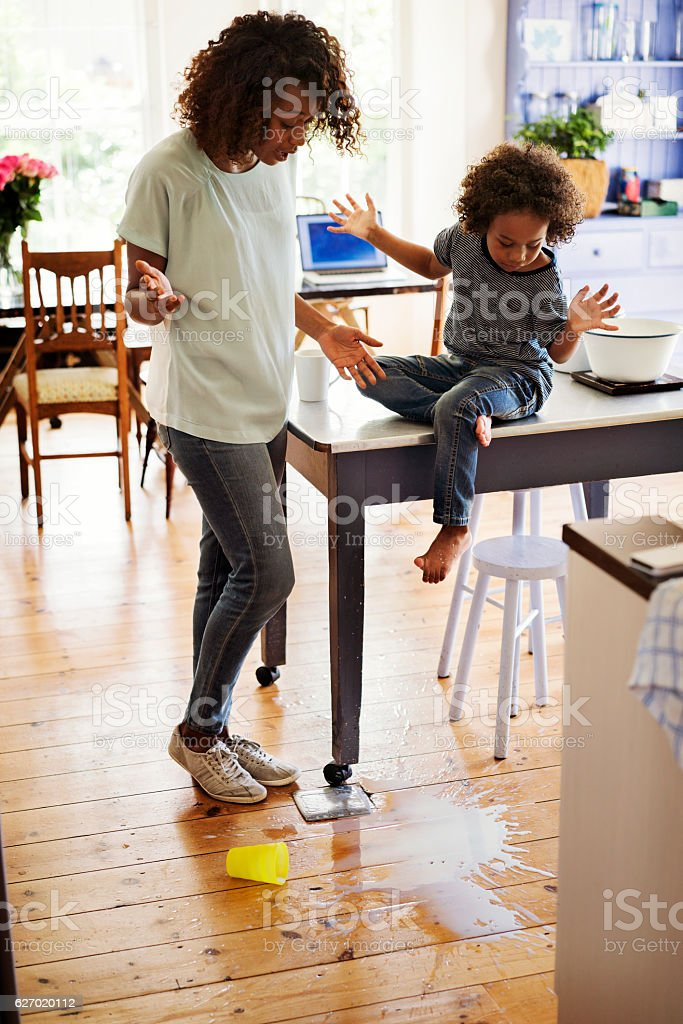 Shocked mother and son looking at fallen milk stock photo
