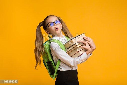 istock Shocked Nerdy Schoolgirl Carrying Heavy Books On Yellow Background 1168369293