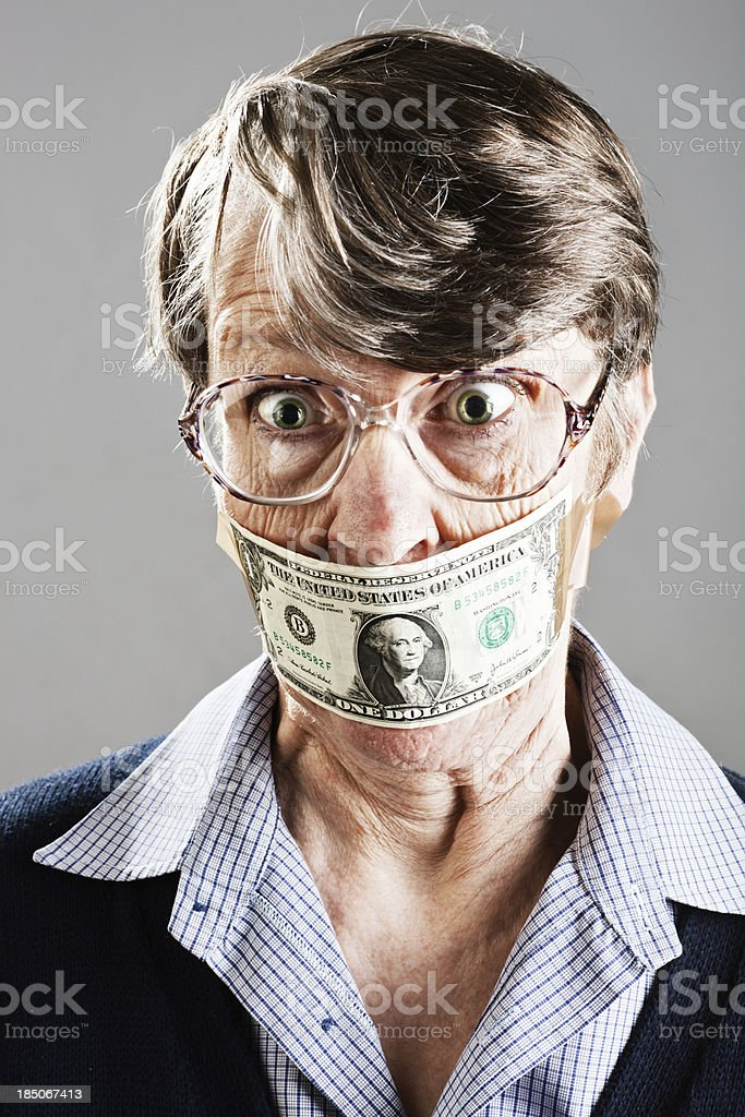 Shocked old woman silenced by US dollar bill gag stock photo