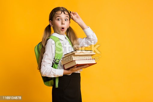 istock Shocked Primary School Girl Holding Stack Of Books, Yellow Background 1169134878