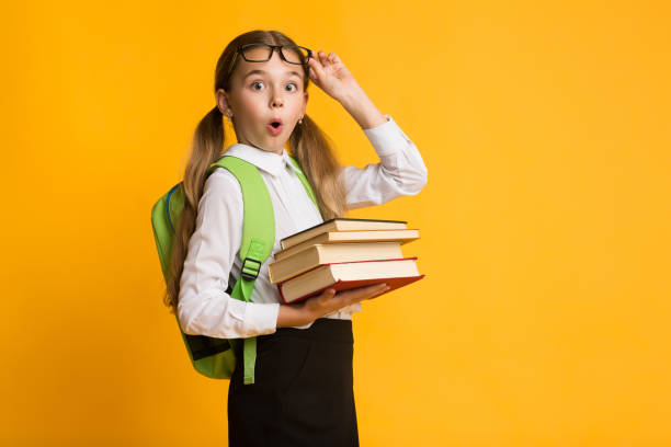 Shocked primary school girl holding stack of books yellow background picture id1169134878?b=1&k=6&m=1169134878&s=612x612&w=0&h=gqaz5wkkms56y8pv50bpnuvzu8nsfcycktz7awlkwes=