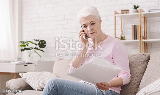 istock Shocked retired woman listening to bank agent with documents 1202700470