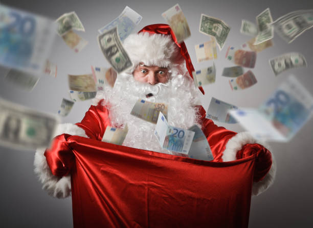 shocked santa claus is looking in to the sack with euro and dollars. consumerism concept. - dollar bill стоковые фото и изображения