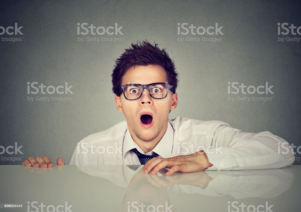 Shocked scared man coming out from under the table stock photo