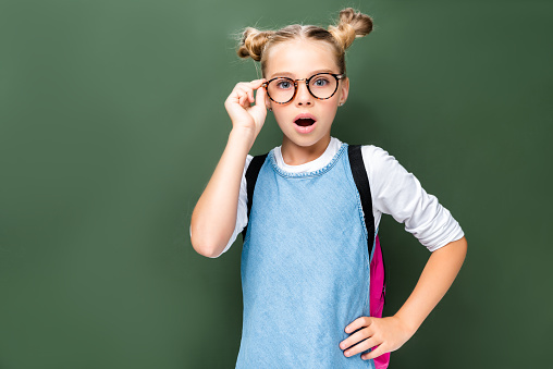 1016623732 istock photo shocked schoolchild touching glasses and looking at camera near blackboard 1016623584