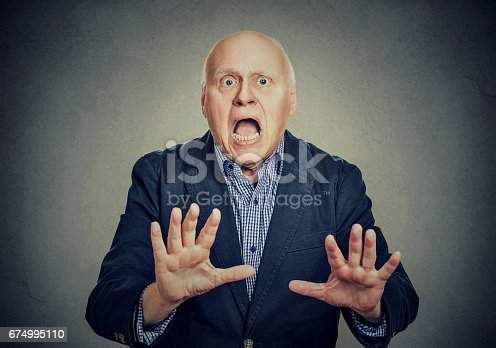 661896674istockphoto Shocked senior man holding his hands out in fear 674995110
