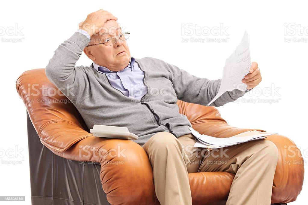 Shocked senior man looking at his bills in disbelief stock photo
