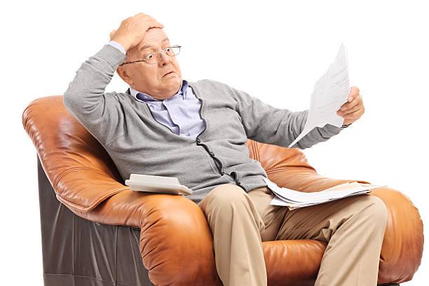 Schockiert senior Mannes Blick in seine Rechnungen in Ungläubigkeit – Foto