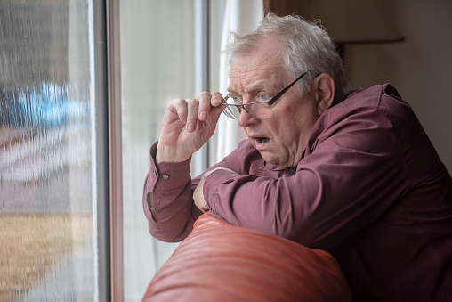 Shocked senior man looking out of window, nosy neighbor