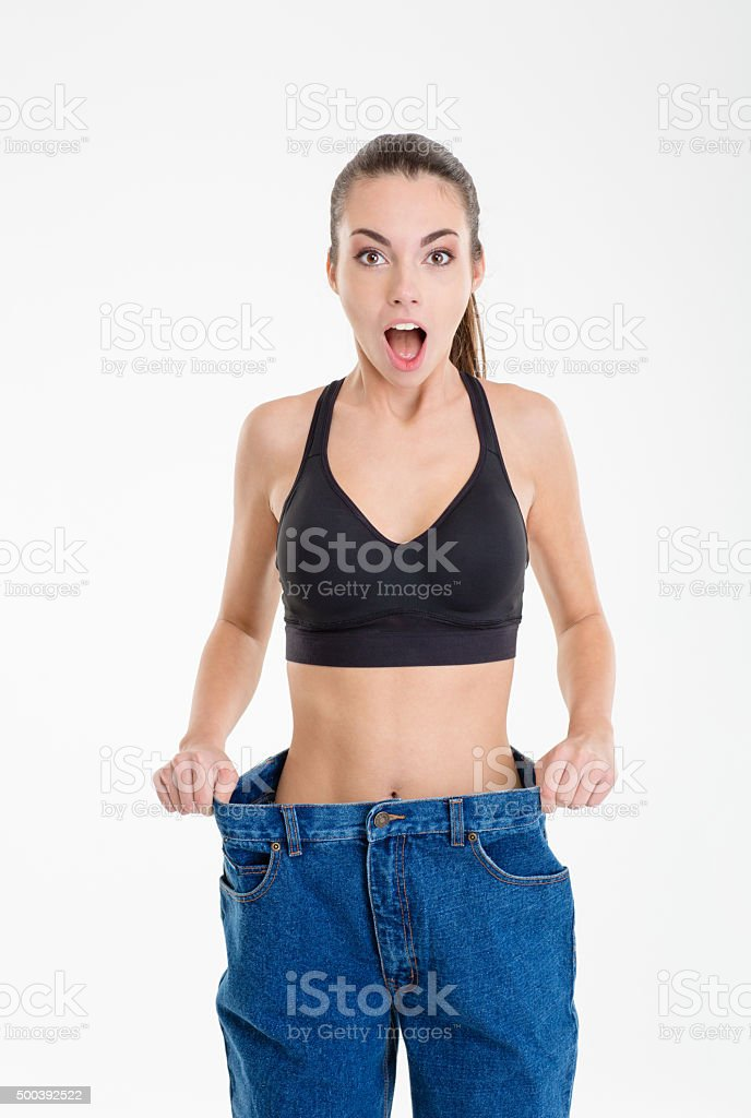 Shocked slim fitness girl in jeans that became too big stock photo