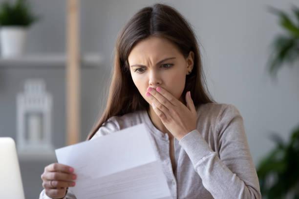 震驚的年輕女子閱讀有關債務的檔信 - 吃驚 個照片及圖片檔