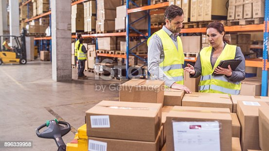 Displeased woman holding a digital tablet pointing at cardboard boxes and giving instructions to an employee in a warehouse. Forklift and other workers visible in the background.