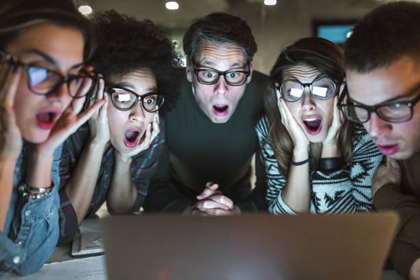 驚心動魄的企業家團隊在辦公室用筆記本電腦閱讀電子郵件。 - 吃驚 個照片及圖片檔