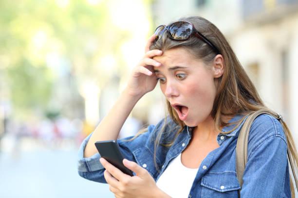 schockiert teen telefon inhaltskontrolle auf der straße - bedauern stock-fotos und bilder