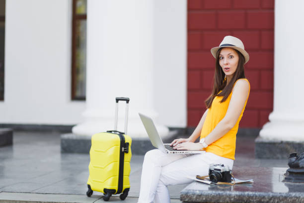 Shocked traveler tourist woman in casual clothes, hat with suitcase sitting using working on laptop pc computer in city outdoor. Girl traveling abroad on weekends getaway. Tourism journey lifestyle. stock photo