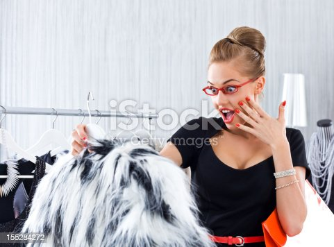 Beautiful young adult woman shopping in luxury boutique, reacting on special price of fur jacket.