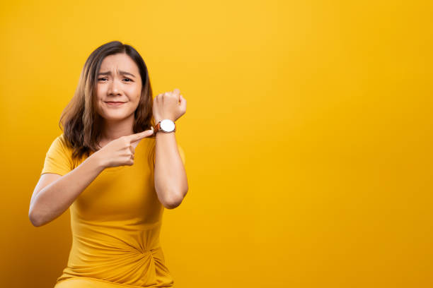 Shocked woman holding hand with wrist watch isolated on a yellow background Shocked woman holding hand with wrist watch isolated on a yellow background overworked stock pictures, royalty-free photos & images