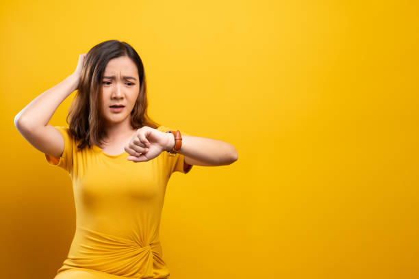 Shocked woman holding hand with wrist watch isolated on a yellow background stock photo