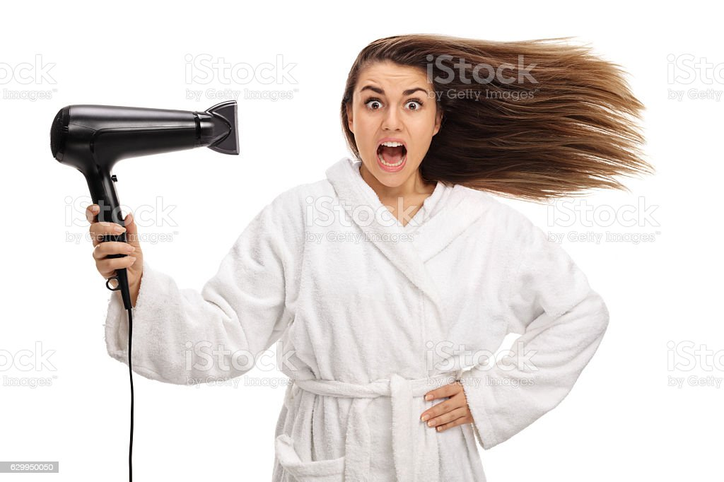 Shocked woman in a bathrobe drying her hair with hairdryer stock photo