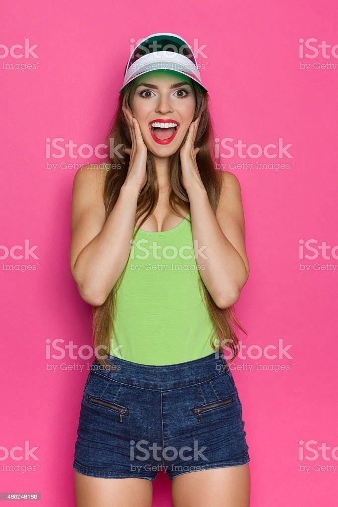 Shocked Woman In Green Shirt And Sun Visor stock photo