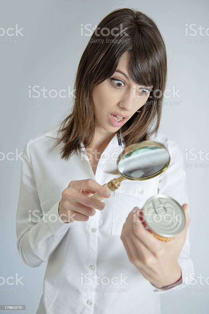 Shocked woman inspecting a nutrition label stock photo
