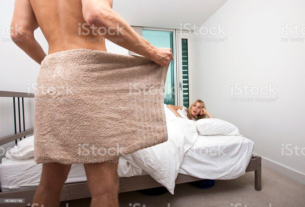 Schockiert Frau Blick Auf Nackte Mann Hält Handtuch Im Schlafzimmer  Lizenzfreies Stock Foto