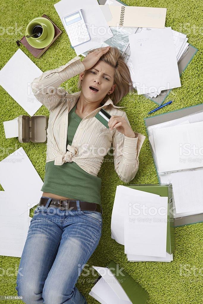 Shocked woman on floor with bills stock photo