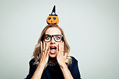 Mid adult beautiful woman wearing black sweater and headband with pumpkin standing against grey background and shouting at camera.