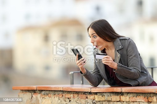 istock Shocked woman shopping online with credit card 1084057306