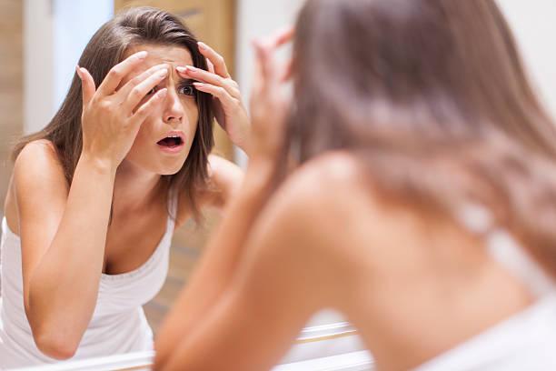 Choqué femme presser Peau boutonneuse dans la salle de bains - Photo