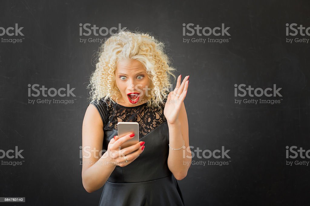 Shocked woman using smartphone stock photo