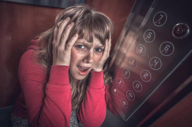 geschokt vrouw met claustrofobie in de verhuislift - claustrofobie stockfoto's en -beelden
