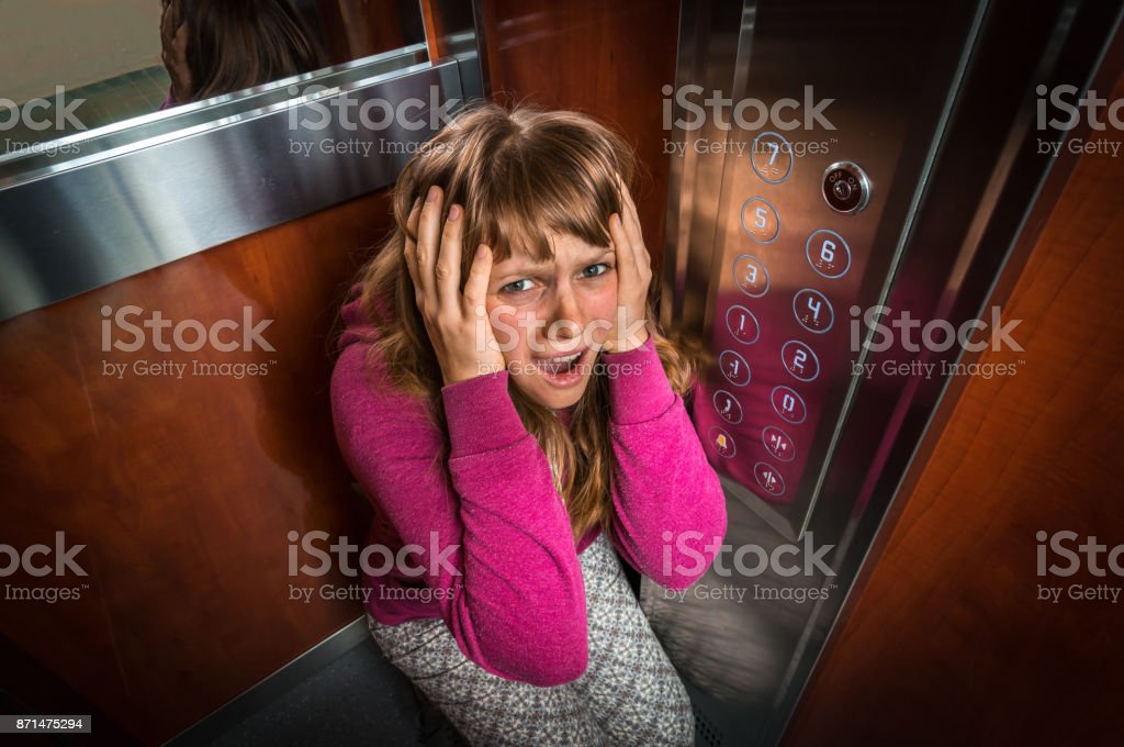 Shocked woman with claustrophobia in the moving elevator stock photo