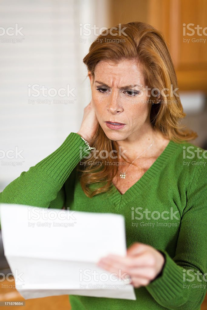 Shocked woman with open mouth reading credit card statement royalty-free stock photo