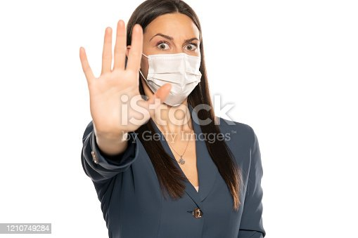 Shocked woman with stop hand and protective mask on her face on white background